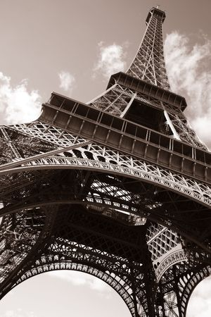 Sepia image looking up from the base of the Eiffel Tower.  There are sky and clouds in the background. Vertical shot.