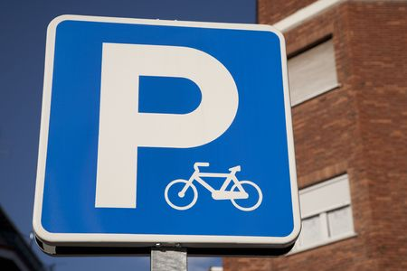 Blue bicycle parking sign in urban setting Stock Photo - 7218259