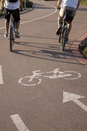 Two cyclists on bike lane keeping fit