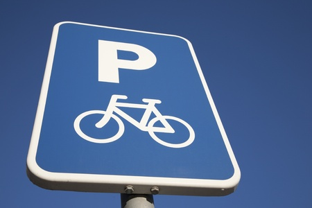 Bicycle Parking Sign against Blue Sky Background photo