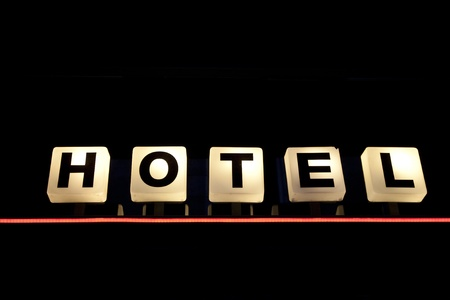 Illuminated Hotel Sign against Black Background Stock Photo
