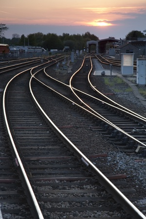 Railroad Tracks at Twilight Running into the Distance Stock Photo