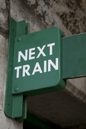 Green Next Train Sign at Railway Station Stock Photo