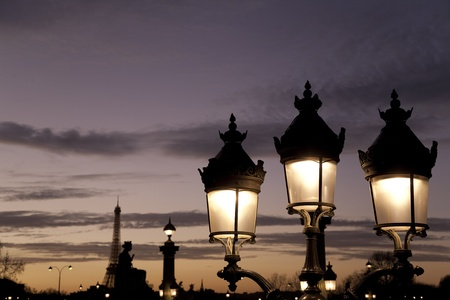 Lamppost illuminated at night and Wiffel Tower in Paris, France