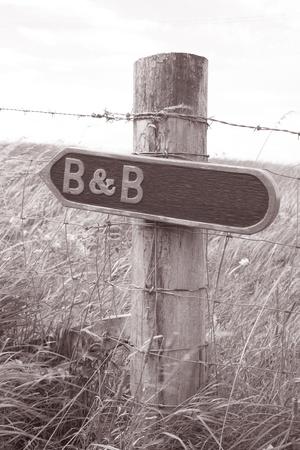 b n: B n B Sign in Rural Setting in Black and White Sepia Tone Stock Photo