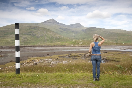 Young Woman looking toward Mountain on Isle of Mull, Scotland, UK