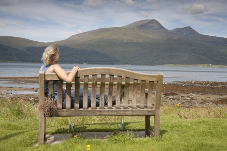 mull: Young Woman sitting on Bench on Isle of Mull; Scotland