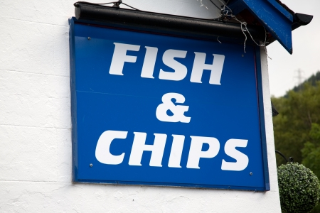 Blue Fish and Chips Sign on White Wall Stock Photo