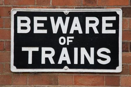 Beware of Train Warning Sign on Brick Wall Banco de Imagens