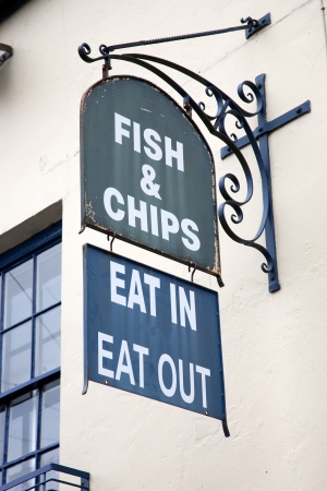 Old Fish and Chips Sign on Building Facade photo