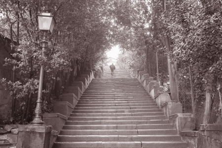 lampost: Man Walking up steps to Michelangelo Square, Florence, Italy in Black and White Sepia Tone