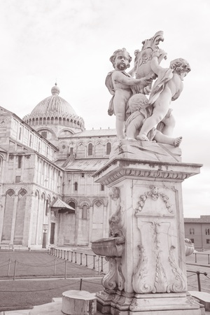 angels fountain: Fountain with Angels - Fontana dei Putti 18th Century and Cathedral of Pisa in Piazza dei Miracoli Square, Pisa, Italy in Black and White Sepia Tone Stock Photo