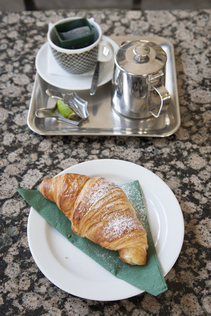 serviette: Croissant and Pot of Tea on Cafe Table with Green Serviette