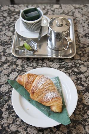 servilleta de papel: Croissant y taza de t� en el vector del caf� con servilleta verde
