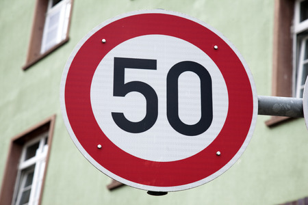 kilometre: Red Fifty Speed Sign in Urban Setting Stock Photo