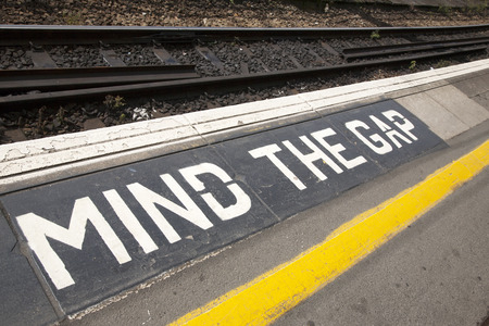 Closeup of Mind the Gap Platform Sign at Railroad Station on Diagonal Tilt Stock Photo
