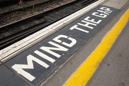Closeup of Mind the Gap Platform Sign at Railroad Station on Diagonal Tilt photo