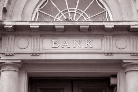 building: Bank Sign over Entrance Door in Black and White Sepia Tone