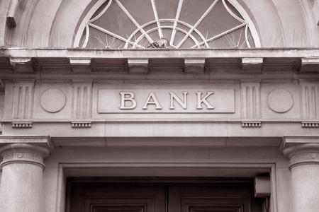 fachada: S�mbolo del Banco sobre la puerta de entrada en tono sepia Blanco y Negro Foto de archivo