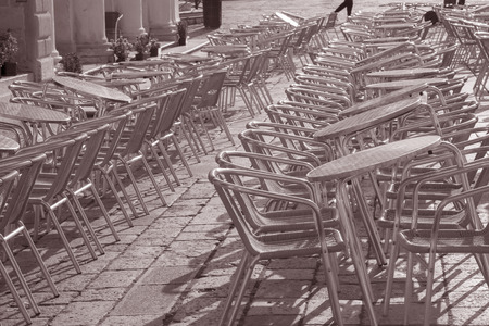 st marks square: Cafe Table and Chairs in St Marks Square; Venice; Italy in Black and White Sepia Tone Stock Photo