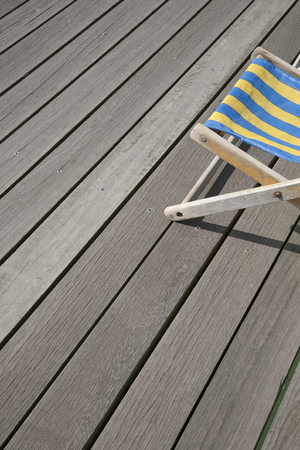 deckchair: Blue and Yellow Deckchair against Wooden Boards Stock Photo