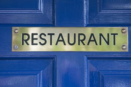 blue door: Gold Restuarant Sign on Blue Door Stock Photo