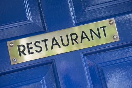 restuarant: Gold Restuarant Sign on Blue Door Stock Photo