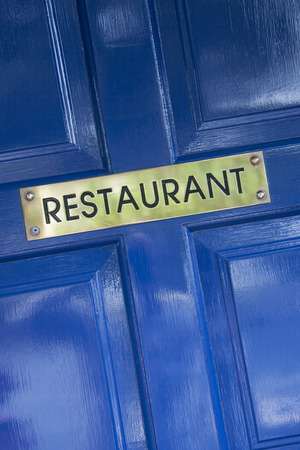restuarant: Gold Restuarant Sign on Blue Door Stock Photo