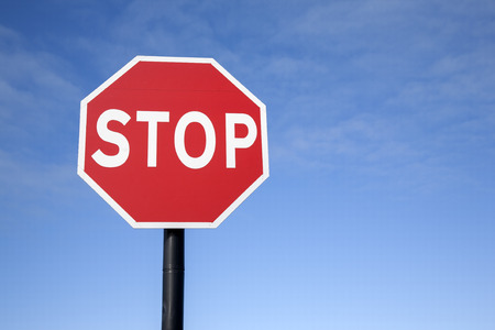 Red Stop Traffic Sign on Blue Sky Background Stock Photo
