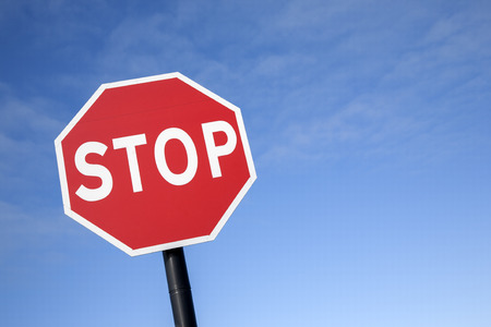 sign: Red Stop Traffic Sign on Blue Sky Background Stock Photo