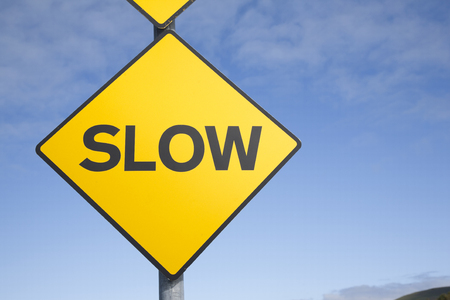 slow: Yellow Slow Sign against Blue Sky Background
