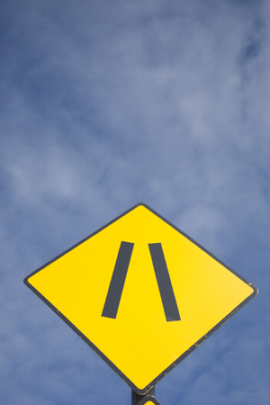 narrowing: Road Narrowing Sign against Blue Sky Background