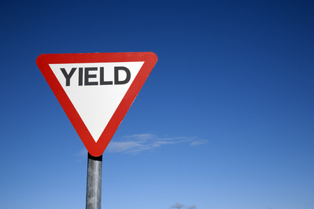 Red and White Yield Sign against a Blue Sky Background Stock Photo