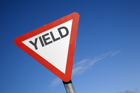 yield sign: Red and White Yield Sign against a Blue Sky Background Stock Photo