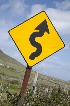 curve road: Curve Road Traffic Warning Sign in Village Setting Stock Photo