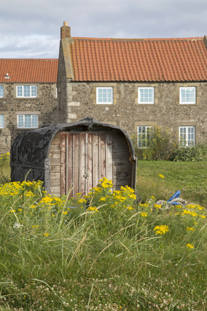 upturned: Upturned Boat used as Shed with Traditional House, Lindisfarne; Holy Island; Northumberland; England; UK Stock Photo