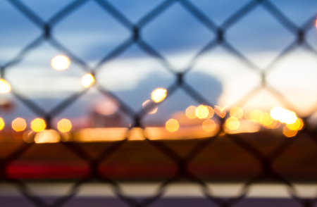 razor wire: Sunset behind the barbed wire - fence with sunset background - strange blue glow in the sky Stock Photo