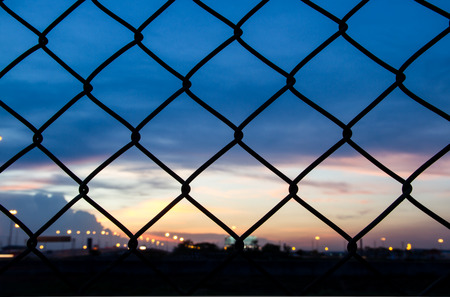 Sunset behind the barbed wire - fence with sunset background - strange blue glow in the sky photo