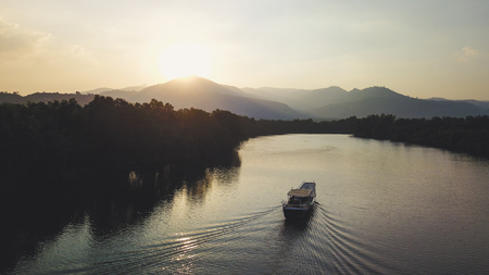 Boat sailing towards Sunset in front of Mountain Ridge. Drone Shot.