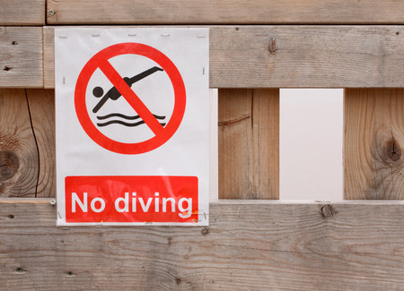 no diving sign: No diving sign stapled on wood