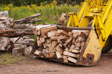 loader: Hydraulic loader bucket filled with firewood  Stock Photo