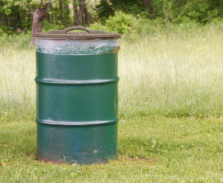 dumps: Green garbage can in rural setting Stock Photo