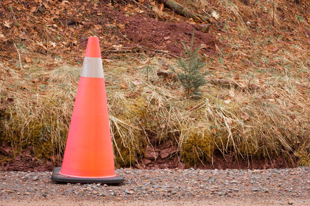 ditch: Traffic cone on a dirt road beside a small ditch  Stock Photo
