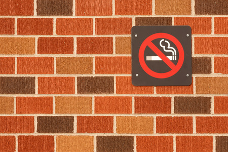 No smoking sign on multi color brick wall photo