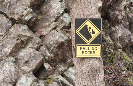rockslide: Falling rocks sign on tree with rocky background Stock Photo