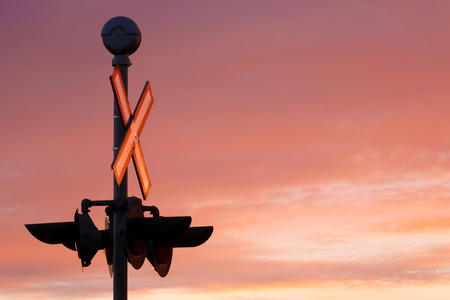 rail cross: Train crossing signal and sign at daybreak