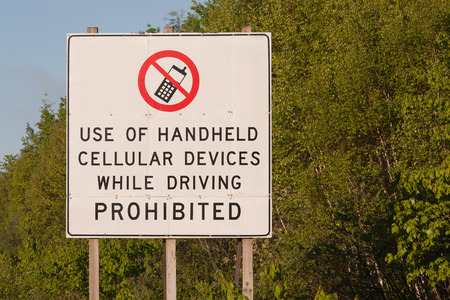 dissuade: Sign - Use of handheld cellular devices while driving prohibited  Stock Photo