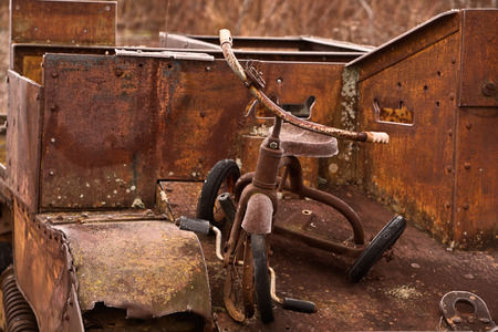 Old and broken tricycle on a rusted World War Two Universal Carrier photo