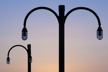 silhoutted: Silhoutted view of boardwalk lamps at daybreak
