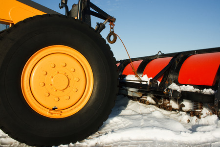 grader: Detail view of snowplough front end with blue sky